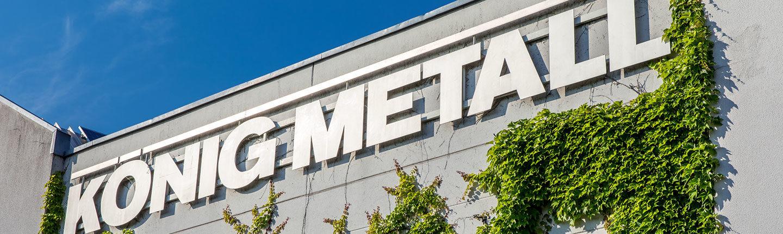metallisches Logo König Metall an Gebäudewand