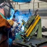 Mitarbeiter mit Schweißmaske schweißt Bauteil